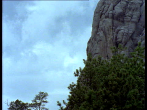 pan right from mountainside to carvings on mount rushmore - felswand stock-videos und b-roll-filmmaterial