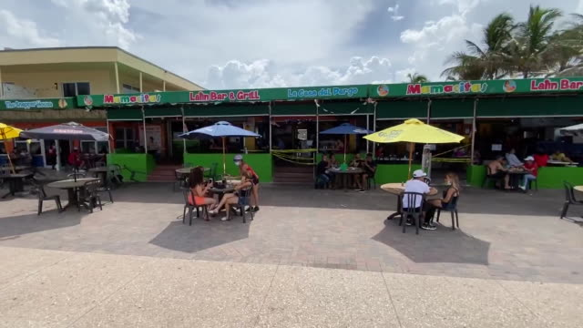 pan right from outdoor dining in front of closed hollywood beach in florida for 4th of july. - july stock videos & royalty-free footage
