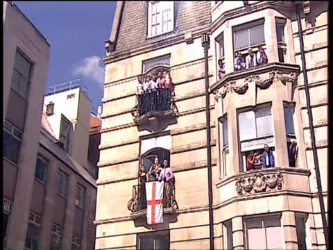 pan right from people gathered at windows to england cricket team in open top bus during ashes victory parade london; 13 sep 2005 - squadra di cricket video stock e b–roll