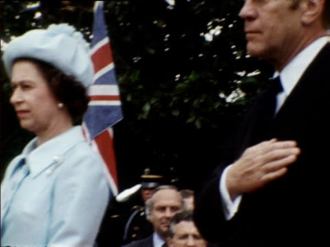 Pan right from Queen Elizabeth II to President Gerald Ford with hand on heart as US National Anthem is played during Queen's state visit to...
