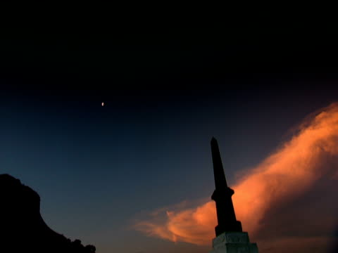 pan right from silhouetted memorial to the 24th regiment at isandhlwana against orange cloud in dark sky with half moon - half moon stock videos & royalty-free footage