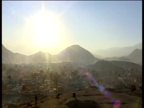 Pan right from sun flare over Kabul silhouetted mountains in distance Afghanistan