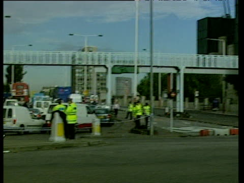 Pan right from traffic queues behind police cordon to MI6 building after it was hit by missile 21 Sep 00