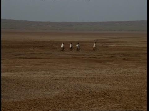 WA pan right, Gujarat, Indian men cycling through desert, Gujarat, India