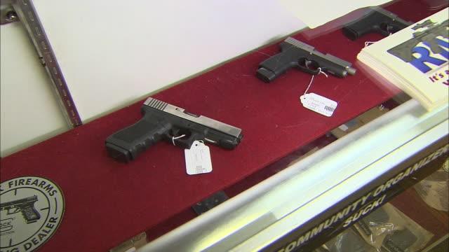 pan right handguns in case at gun shop - gun shop stock videos & royalty-free footage