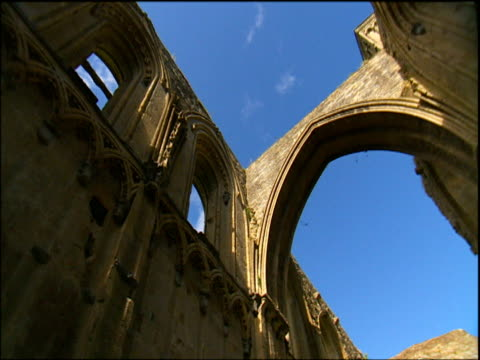 Pan right looking up at ruins of Glastonbury Abbey Somerset