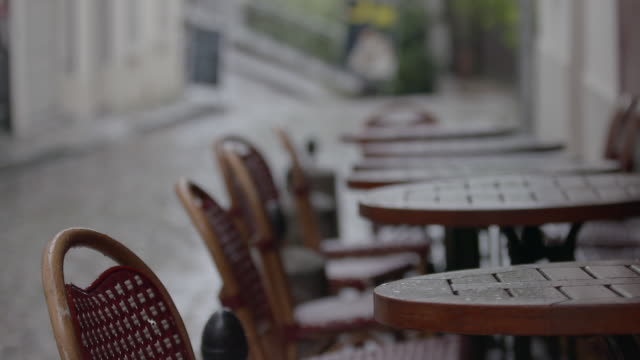 vidéos et rushes de pan right of rain soaked chairs and tables outside a cafe in paris, france - chaise