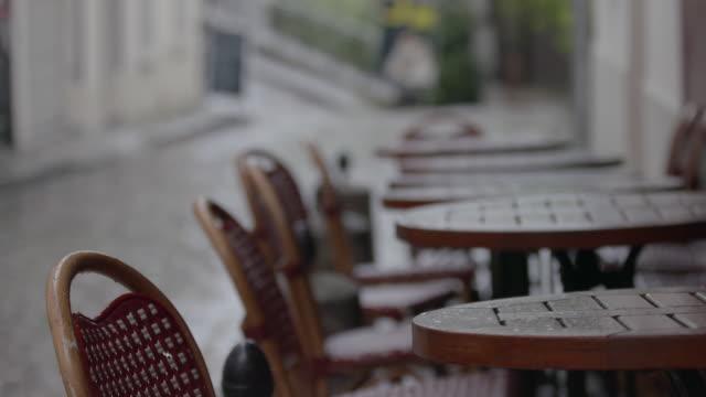 vidéos et rushes de pan right of rain soaked chairs and tables outside a cafe in paris, france - mouillé