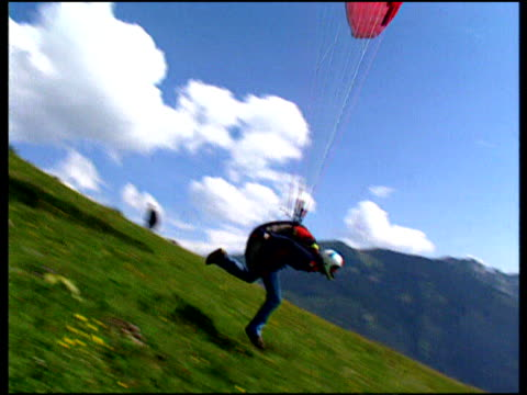 Pan right on para glider wearing crash helmet launching himself off side of steep hill
