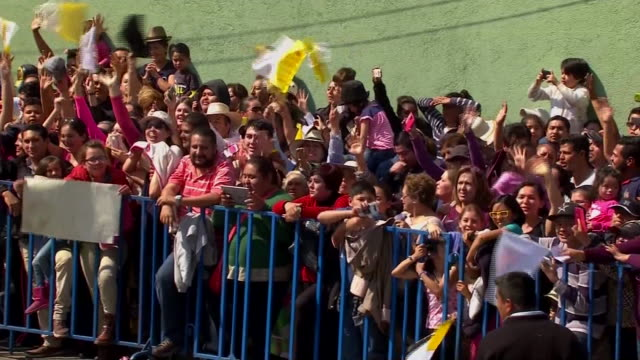 pan right on row of supporters crowded behind barricade as pope francis arrives in morelia, mexico - morelia video stock e b–roll