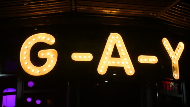 Pan right onto the illuminated 'G-A-Y' nightclub sign on Canal Street in Manchester at night