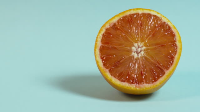Pan right onto, then off, a cross-section of an orange against a plain blue background.