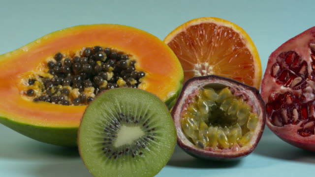 Pan right onto, then off, a group of tropical fruit including papaya, kiwi, passion fruit, orange and pomegranate.