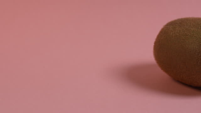 Pan right onto, then off, a whole kiwi fruit on a plain pink background.