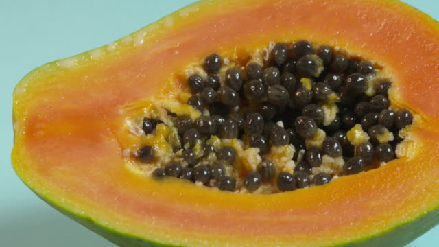 pan right onto, then off, then left onto, then off, a halved papaya against a pale blue studio background. - papaya stock videos & royalty-free footage