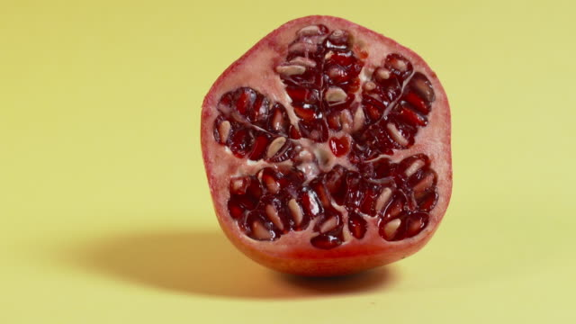 Pan right onto, then off, then pan left onto, then off, a halved pomegranate against a plain, pastel-yellow background.