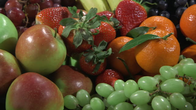 Pan right over a bowl containing a variety of popular fruits.
