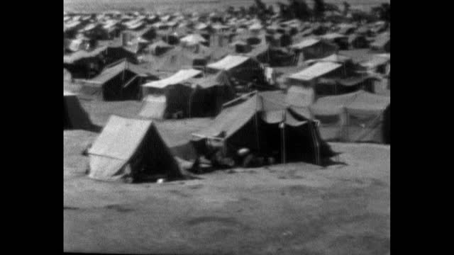 pan right over a huge field of tents set up as a refugee camp near the river jordan and amman for people fleeing conflict in the arab-israeli war;... - simple living stock videos & royalty-free footage