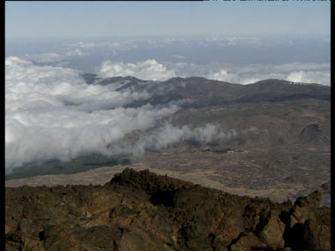 pan right over barren and rocky landscape with clouds in background tenerife. - 大西洋諸島点の映像素材/bロール