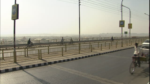 pan right over bridge to kumbh mela pilgrim encampment on dry ganges riverbed, india - riverbed stock videos & royalty-free footage