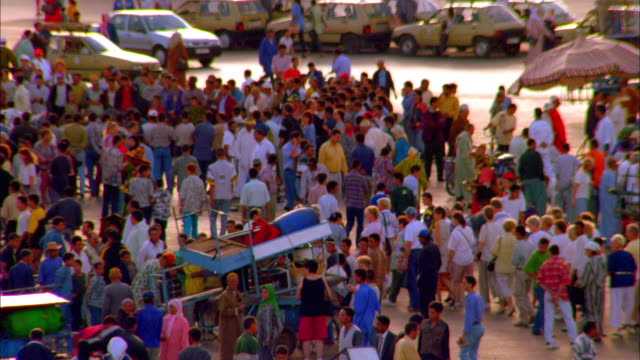 Pan right over busy market by the side of road, crowds of people and men pulling trolley's laden with goods. Available in HD.