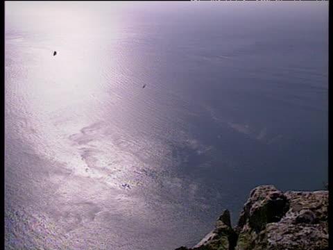 stockvideo's en b-roll-footage met pan right over calm sea and rocky shore rock of gibraltar - gibraltar iberisch schiereiland