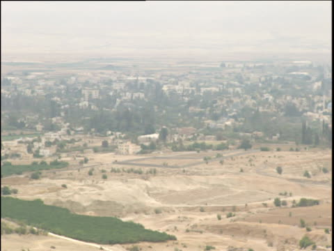 Pan right over city surrounded dry fields in misty light. Jericho Israel