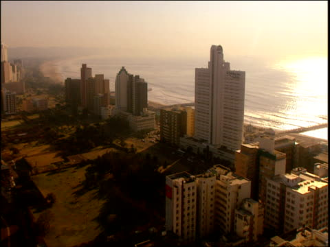 Pan right over cityscape and coast with sun shining on the water