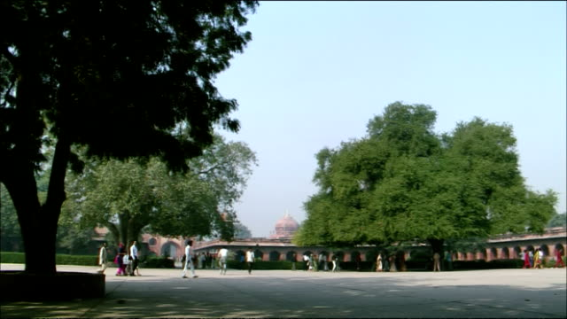 pan right over courtyard to southern gate of taj mahal, agra - mausoleum stock videos and b-roll footage