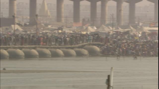 pan right over crowds of kumbh mela pilgrims on ganges floating bridge, india - 緊急用具点の映像素材/bロール