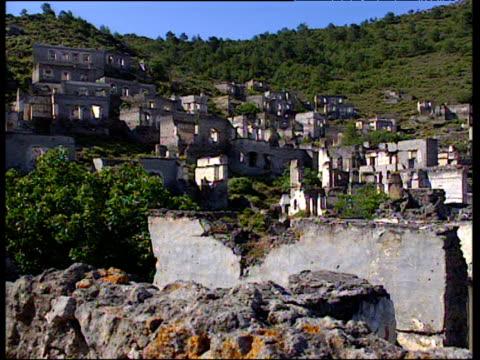 vidéos et rushes de pan right over deserted village stone houses in ruins on hillside - turquie