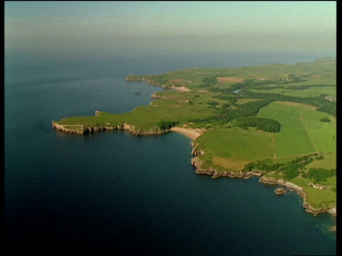 vídeos de stock e filmes b-roll de pan right over green fields of pembrokeshire coastline leading to irish sea - pembrokeshire