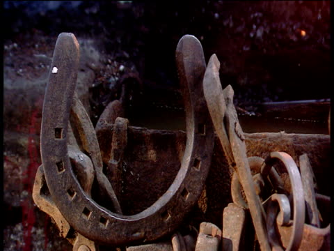 pan right over horseshoe and other paraphernalia in a blacksmith's forge. - horseshoe stock videos and b-roll footage