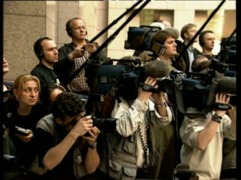 Pan right over journalists photographers and camera crews behind barrier; May 2000