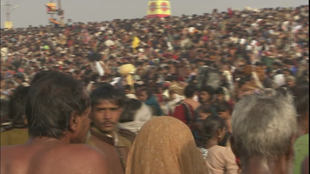 Pan right over large crowd of Kumbh Mela pilgrims, Allahabad, Uttar Pradesh, India