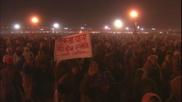 Pan right over large crowd of Kumbh Mela pilgrims walking through Allahabad, Uttar Pradesh, India