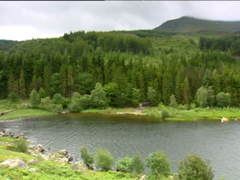 pan right over large lake surrounded by trees and mountains - snowdonia stock videos & royalty-free footage