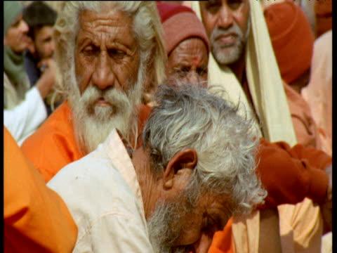 stockvideo's en b-roll-footage met pan right over long line of people sit eating during kumbh mela, allahabad, india - in kleermakerszit