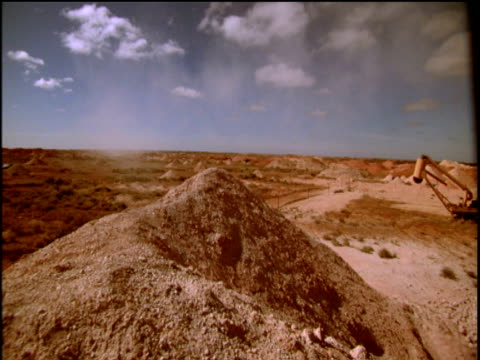 pan right over mounds of excavated earth at opal mine to truck coober pedy - coober pedy stock videos & royalty-free footage