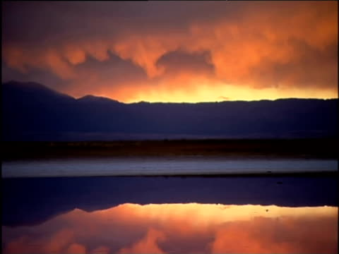 Pan right over mountains reflected in lake silhouetted against orange sunset Chile