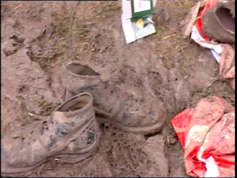 Pan right over muddy shoes and litter at Glastonbury Festival; Jun 05