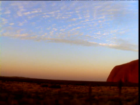 Pan right over outback to Uluru at dusk, Northern Territory, Australia