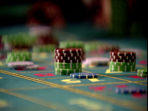 pan right over piles of coloured gambling chips on green baize covered casino table - casino stock videos & royalty-free footage