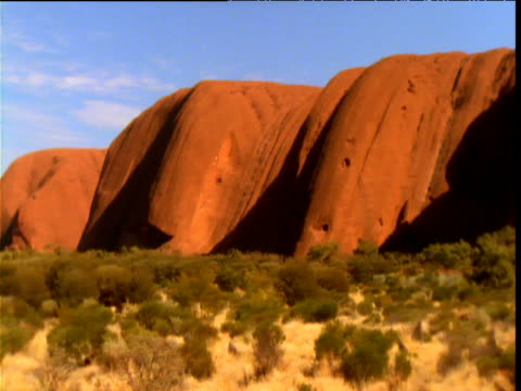 Pan right over red sandstone of Uluru in outback, Northern Territory, Australia