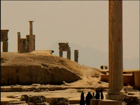pan right over ruins of persepolis including some tourists - persepoli video stock e b–roll