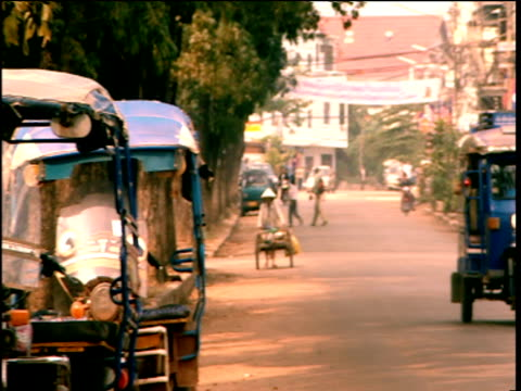 Pan right over street with tuk-tuk travelling down road Laos