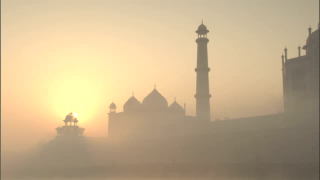 Pan right over Taj Mahal in mist at sunrise Available in HD.