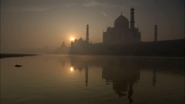 vídeos de stock e filmes b-roll de pan right over taj mahal in mist at sunrise available in hd. - taj mahal