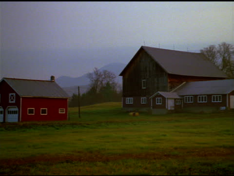 Pan right past farmhouses and barns to fields and trees, Vermont