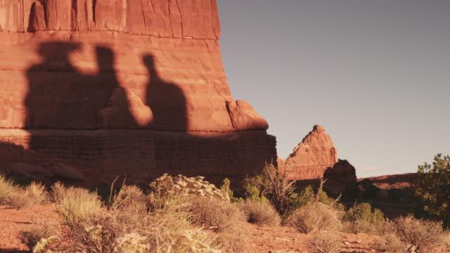 vídeos de stock e filmes b-roll de pan right, shadows of rock formations on utah cliffside - paredão rochoso